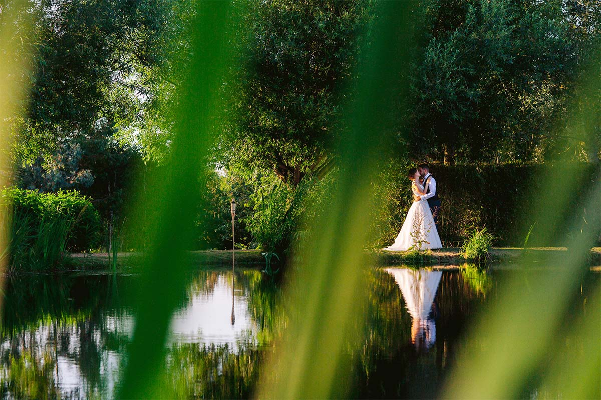 white-villa-photography-bride-groom-kiss-on-the-pond